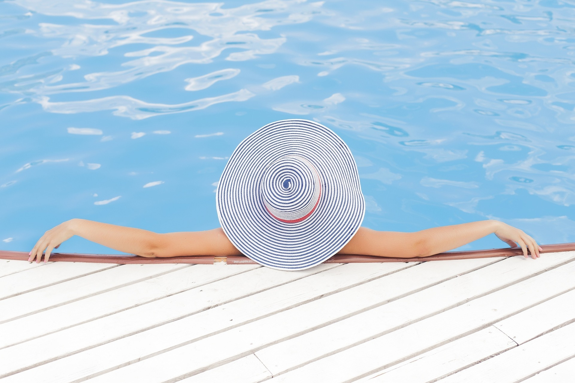 Lady with hat, sat in the pool