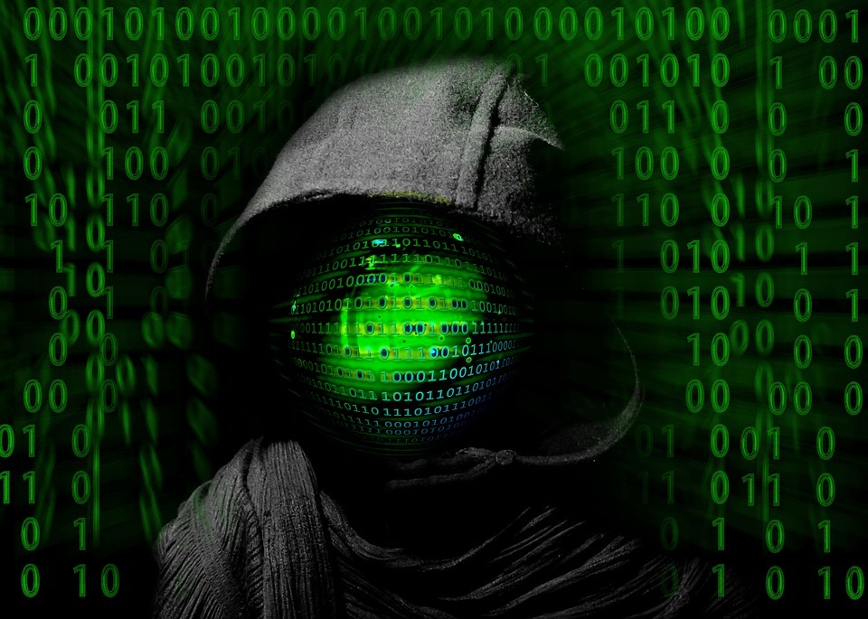 computer hacker in dark hoody with data in green behind & covering face