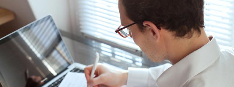 How to apply for a Solicitor Training Contract. Featuring a male Paralegal with brown curly hear wearing glasses and a white shirt as he writes and submits Solicitor training contract applications to prospective employers. Search Consultancy.