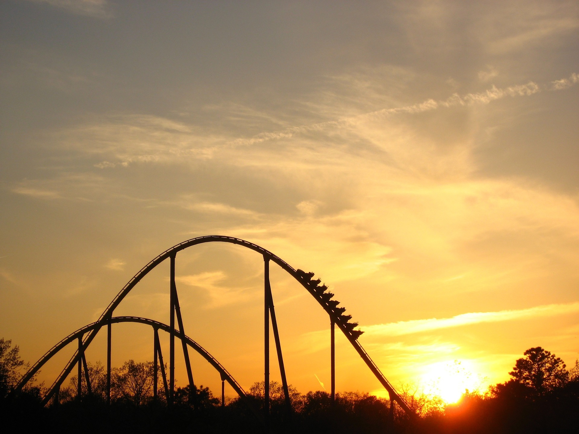 Sunset with a silhouette of a rollercoaster.