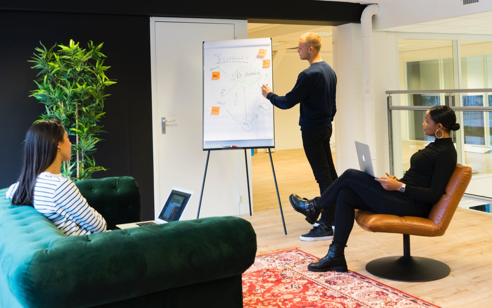 Man standing in front of a whiteboard talking to two women