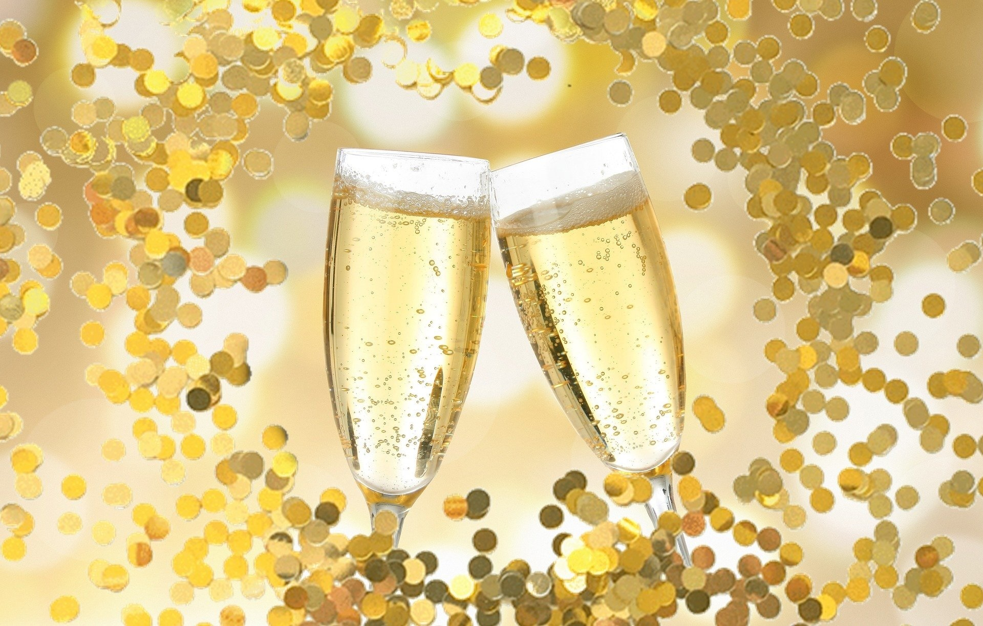 two full champagne glasses next to each other with gold confetti