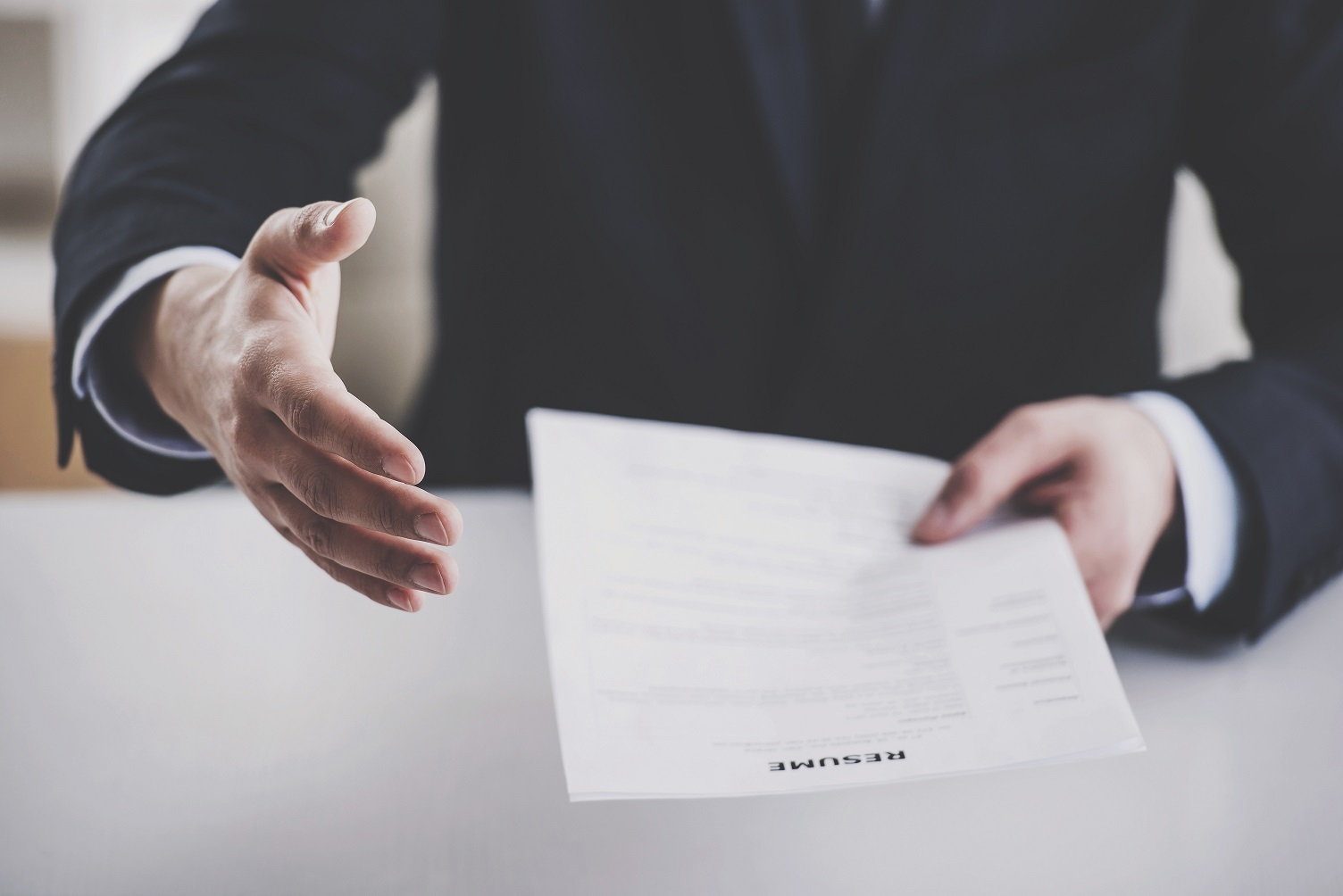 Man in a suit holding out a contract