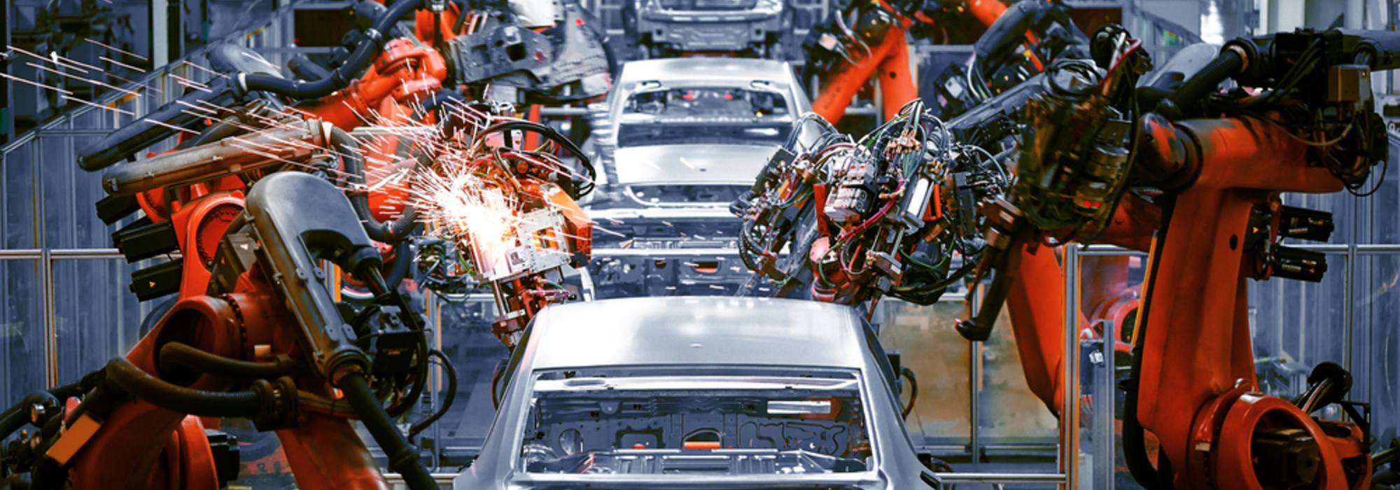 An automotive production line, with cars being built by robotic arms