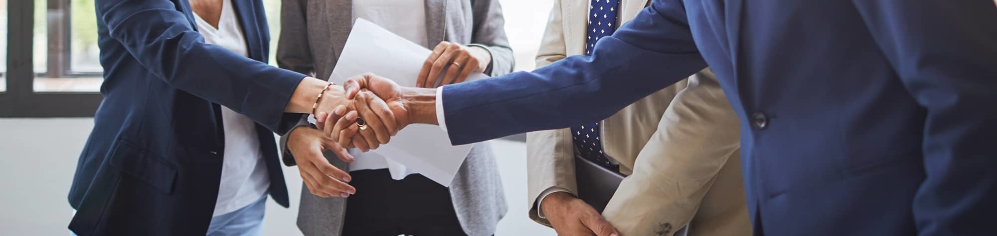 Search Services Header Image. Featuring a professional female recruiter in a blazer shaking the hand of a professional, female candidate. Showcasing the exceptional recruitment services we deliver to candidates and clients at Search Consultancy.