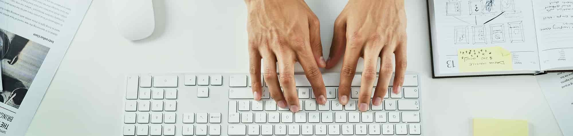 Search Consultancy's Main Blog Page Header Image. Featuring Male Hands Typing On A Laptop Keyboard.