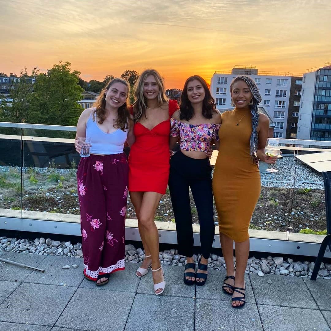 4 girls smiling a the camera at sunset