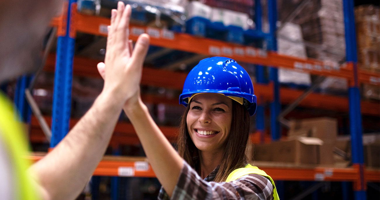 Warehouse workers giving high five to each other