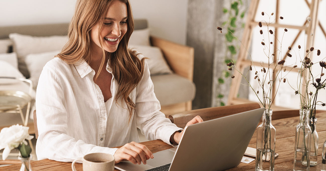 Young cheery happy positive business woman working at home on laptop